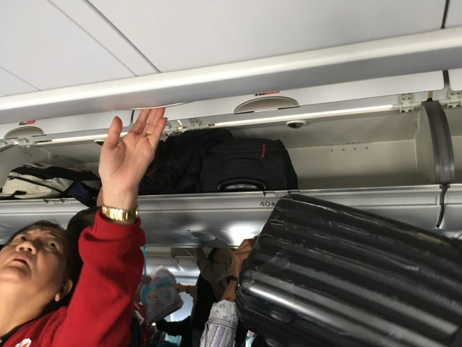 People putting their luggage away in the overhead lockers