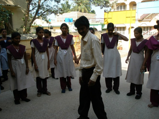 A teenage Indian schoolboy in the centre of a circle of teenage schoolgirls dancing