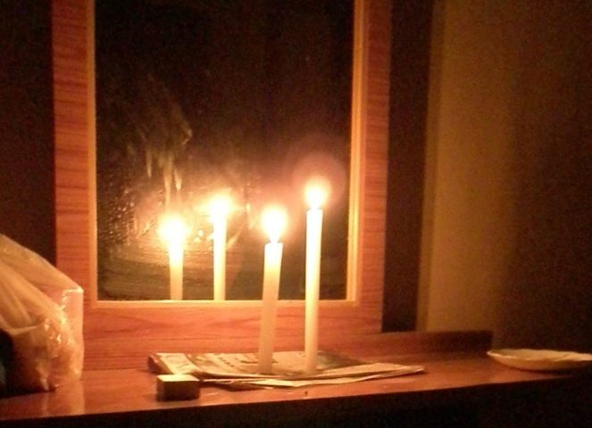 2 thin lit candles in front of a mirror