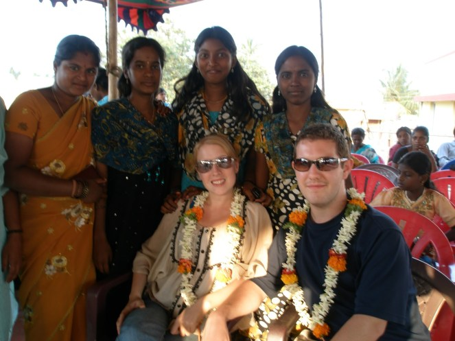 Karl & Rosie sit posing for a photo with flower garlands with 4 young Indian ladies posing behind