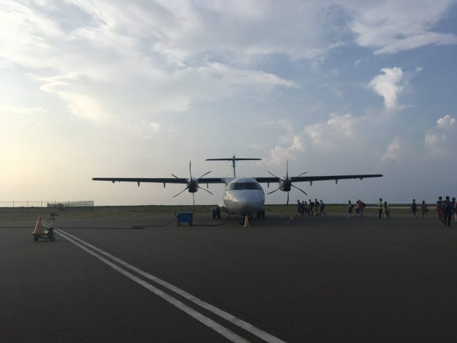 A Flyme ATR 72-500 plane on the tarmac with passengers boarding