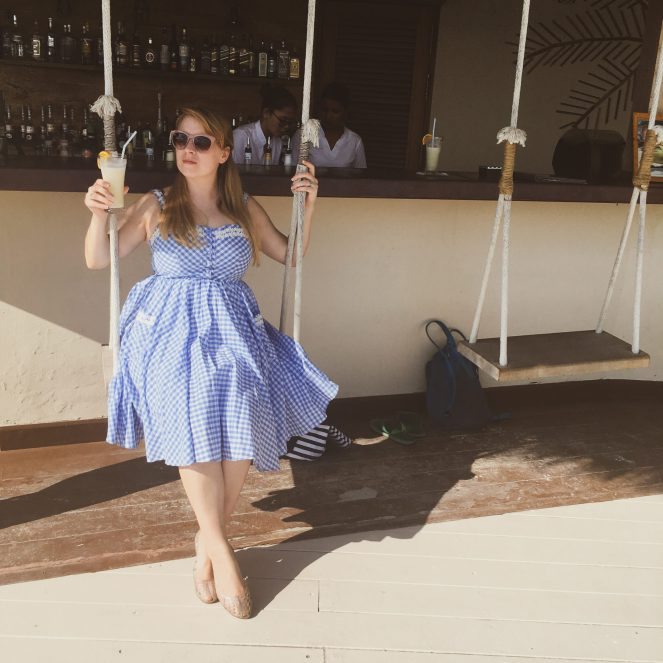Rosie with a drink in a blue dress and sunglasses on a swing seat by the Undhoali bar at Kihaa Maldives