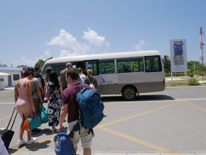 Tourists queue to board a minibus with their hand luggage in the Maldives