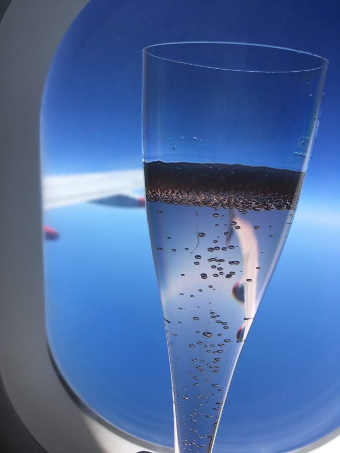 Prosecco bubbles in a flute in front of a aeroplane window on a British Airways Airbus A320