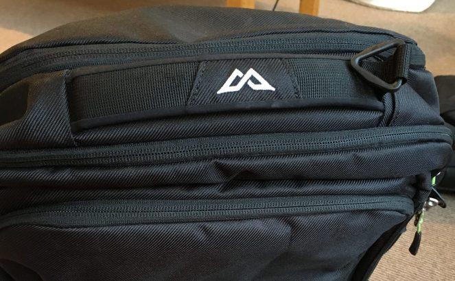 A white logo on the top handle of a black Kathmandu Litehaul 38L backpack