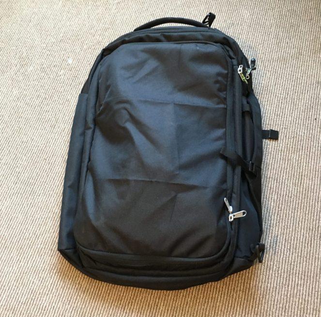 The strap cover on the back of a black Kathmandu Litehaul 38L Backpack