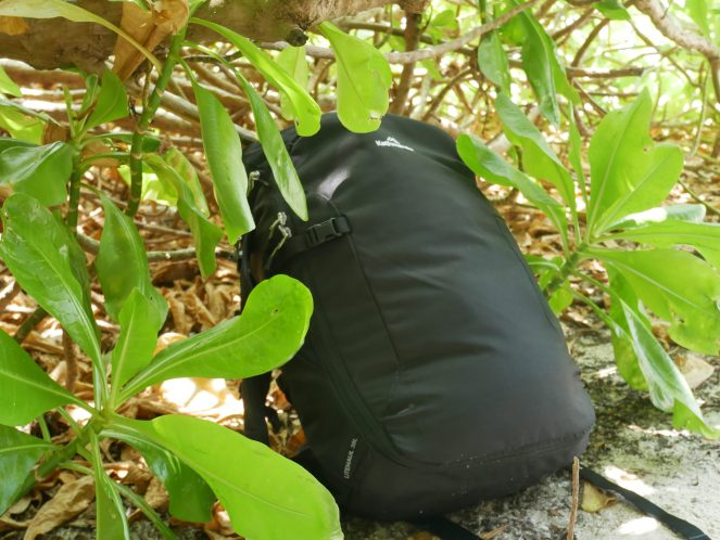 a black Kathmandu Litehaul 38L Backpack on the ground next to bushes in the Maldives