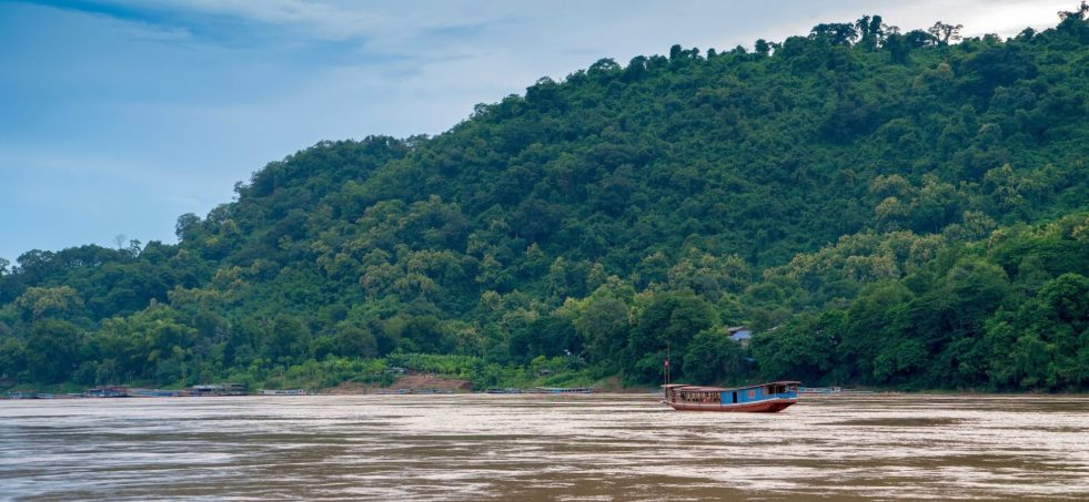 A slow boat on the Mekong River with a tree covered hill in the background