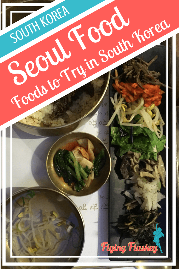 bibimbap with bronze bowls of bulgogi beef on rice, fermented soy beans and a black rectangular plate of vegetables at Mokmyeoksanbang restaurant. Top left a blue and red diagonal banner with white text reads 'South Korea. Seoul Food. Foods to try in South Korea'