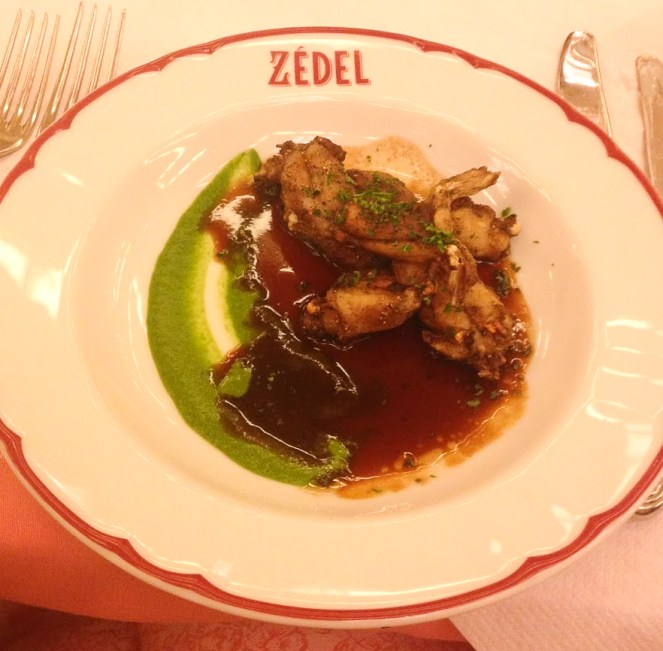 A white dinner plate, with a red rim and Zedel in red writing. Meat in a rich brown sauce with a stripe of green pureed veg down one side at Zedel Brasserie, Soho, London