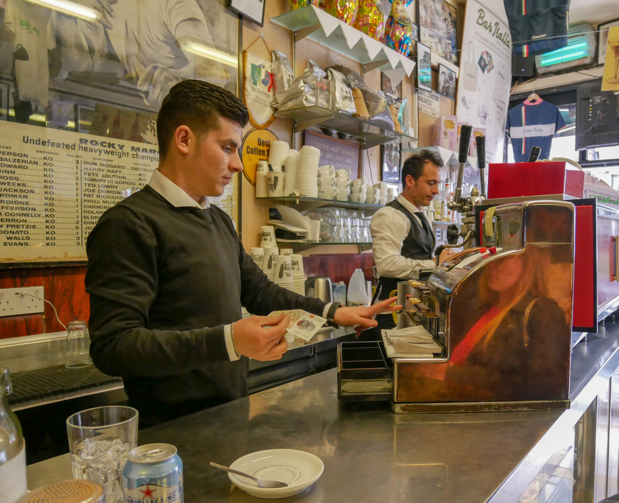 a server puts money into an old till on the counter at Bar Italia, Soho, London