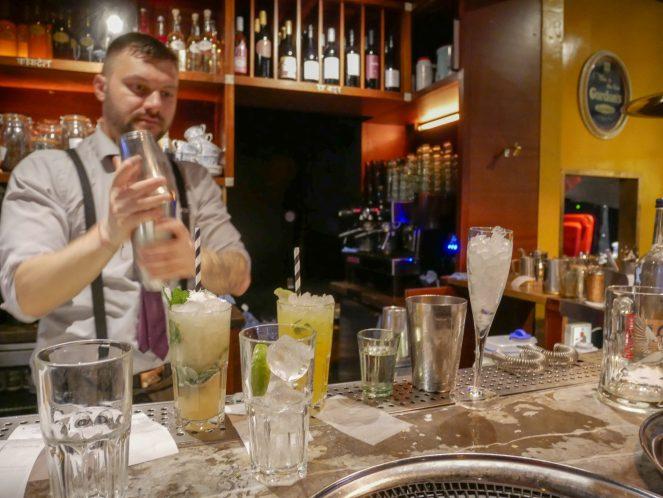 a barman shakes a cocktail shaker at the bar in Dishoom, Soho, London