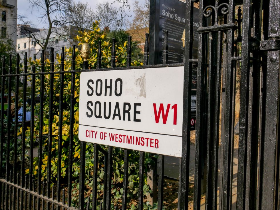 Street sign of Soho Square attached to black metal railings