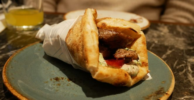 A lamb and tzatziki souvlaki wrap on a plate at Suvlaki, Soho, London