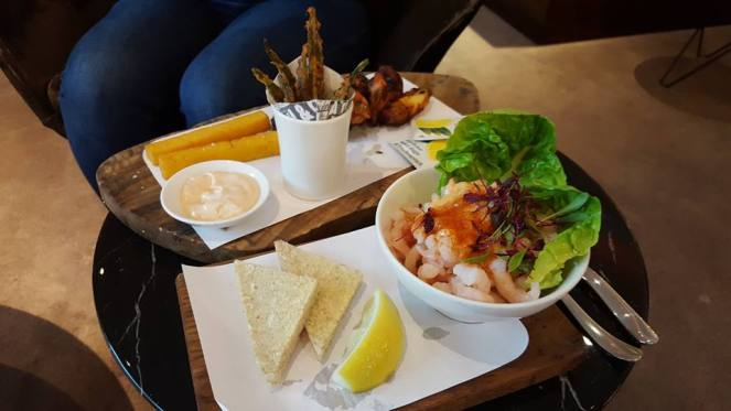 a prawn cocktail in a bowl with 2 triangles of white, buttered bread and a wedge of lime, chicken wings and polenta fries in the Virgin Atlantic Clubhouse London Heathrow Airport Terminal 3