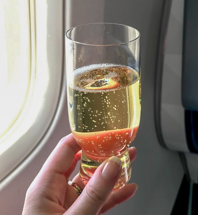 a glass of champagne against the window of a plane