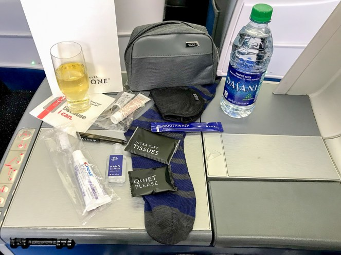 glass of champagne, Dasani water bottle and grey Tumi anemity kit spread out on a tray table on Delta One Delta Air Lines