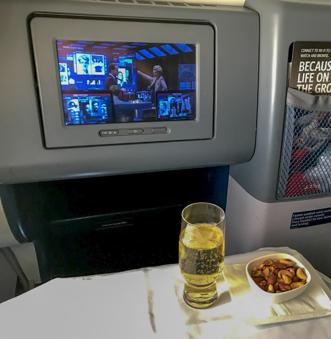 a glass of champagne and a white bowl of nuts in front of the grey IFE screen on Delta One on Delta Air Lines Boeing 767