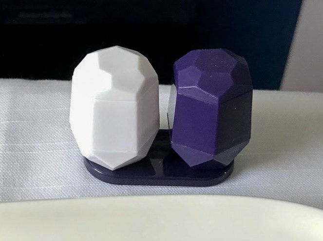a white and blue plastic salt and pepper pots on Delta One Delta Air Lines