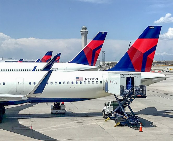 Delta Air Lines Airbus A321-200 plane and other Delta tails behind lined up on stands at Salt Lake City Airport