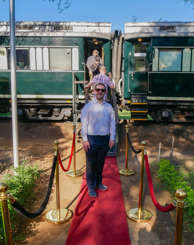 Karl on the red carpet to the entrance of the Royal Livingstone Express train