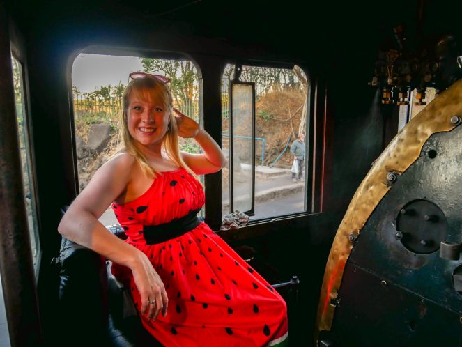 Rosie, in a red dress, sits in the drivers seat of the Royal Livingstone Express train