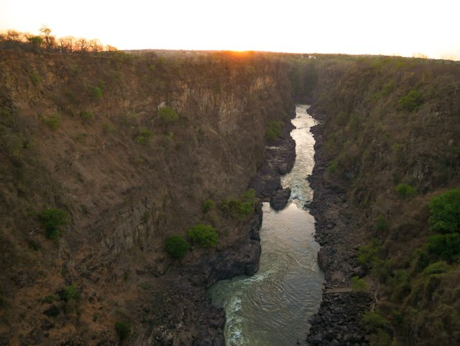 The sun sets over the Victoria Falls gorge with Victoria Falls Hotel in the distance