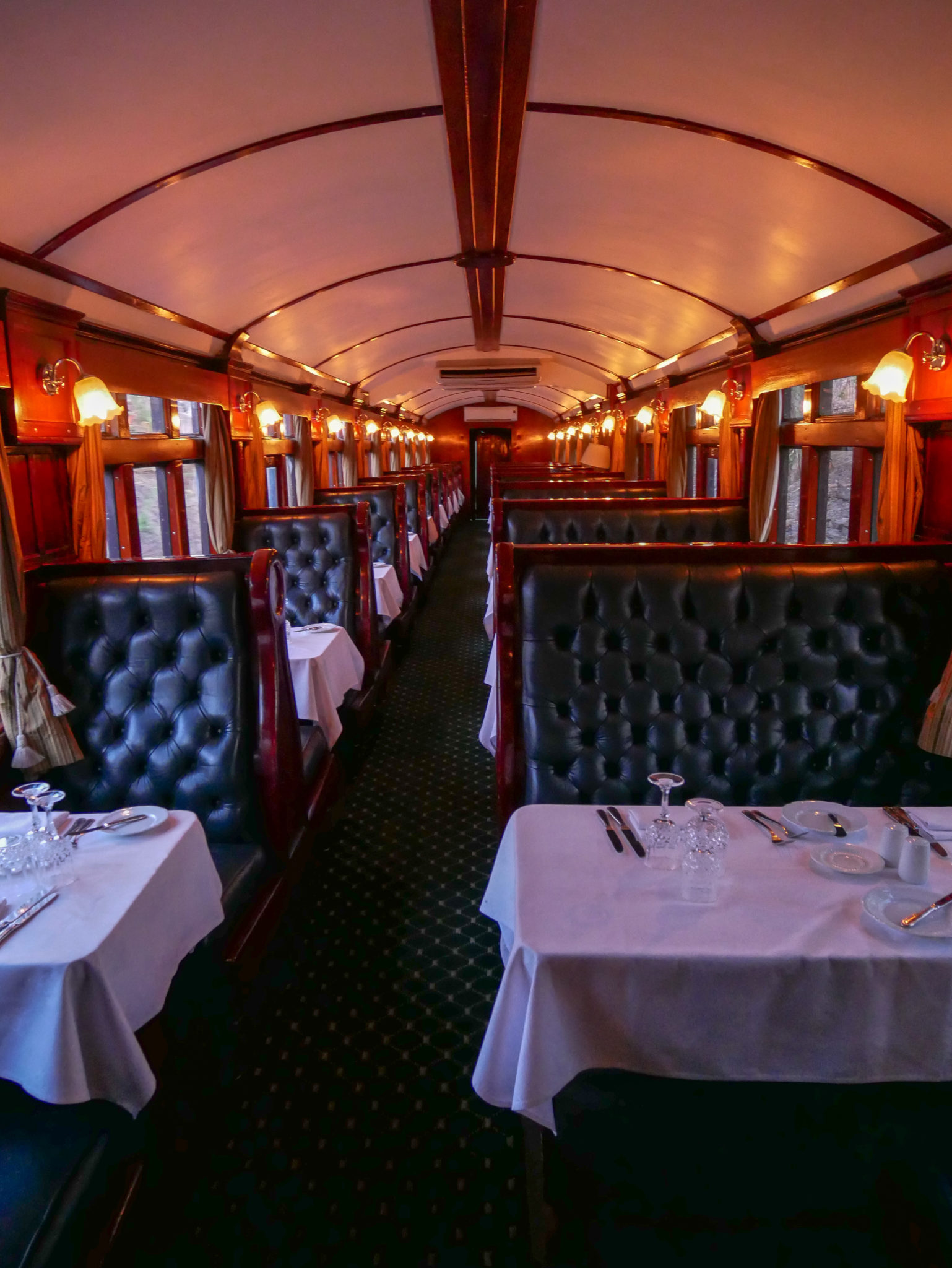 Tall black leather seats and white tablecloths in the Dining Car of the Royal Livingstone Express train