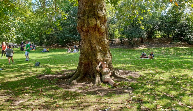 Rosie wearing a green dress sits at a tree in St James's Park