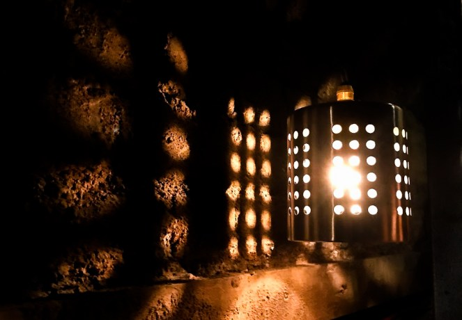 A metal lamp with light creating pattterns across a stone wall