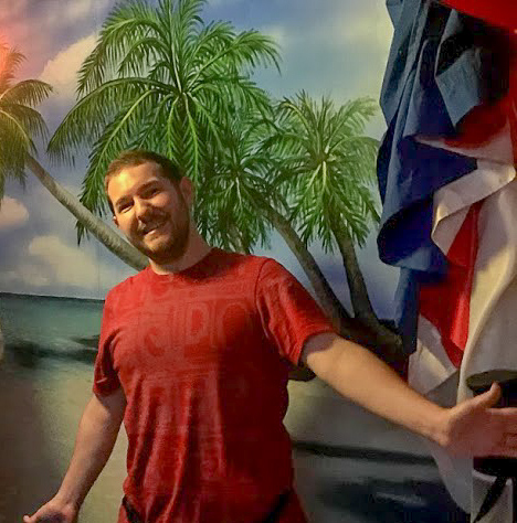 "Mr Fluskey grinning infront of a trpoical island backdrop, arms outstretched in a ""yay, we did it"" sort of a way."