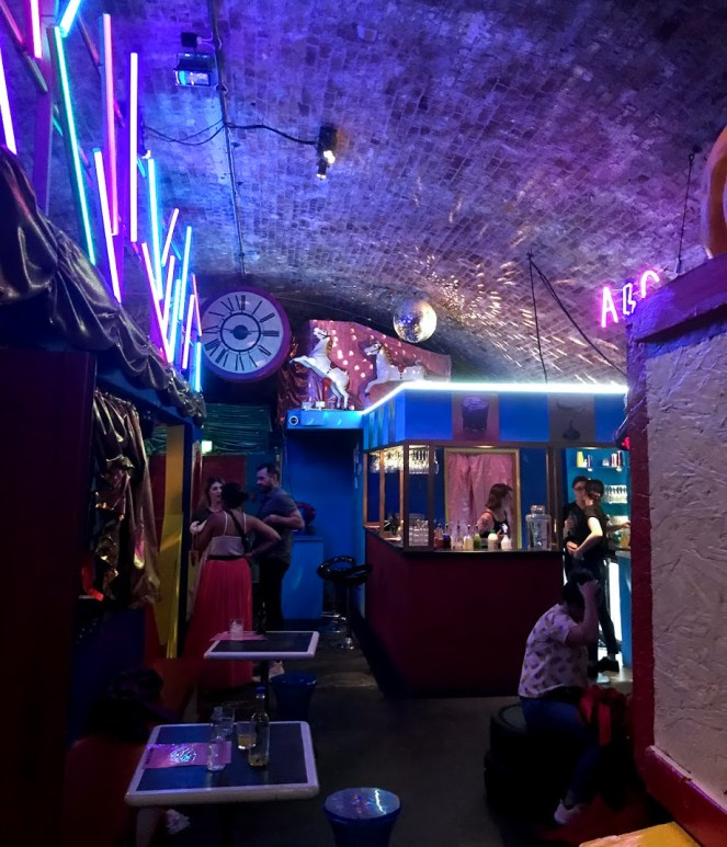 A neon-lit brick archway turned into a fun carnival bar