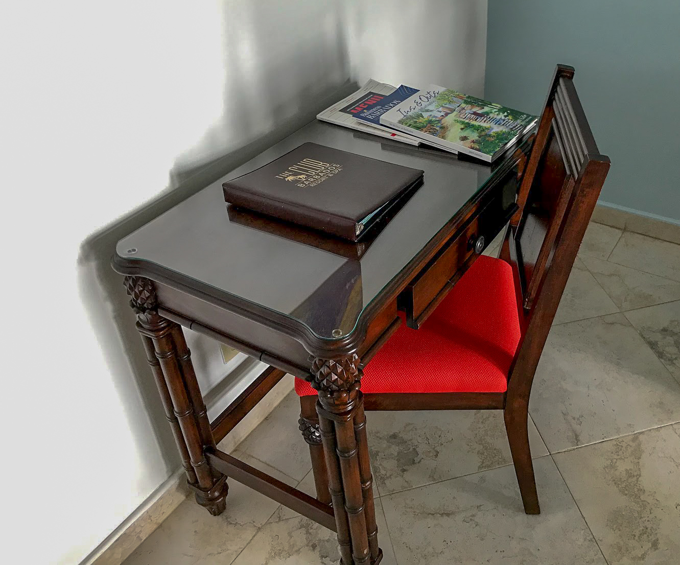 A heavy wooden desk with padded chair in front of it