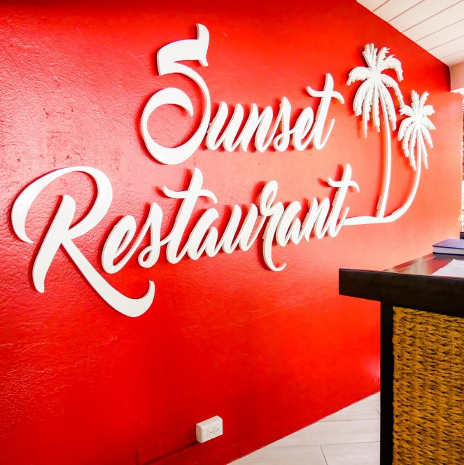 A bright red wall with the Sunset Restaurant logo in huge, raised white lettering