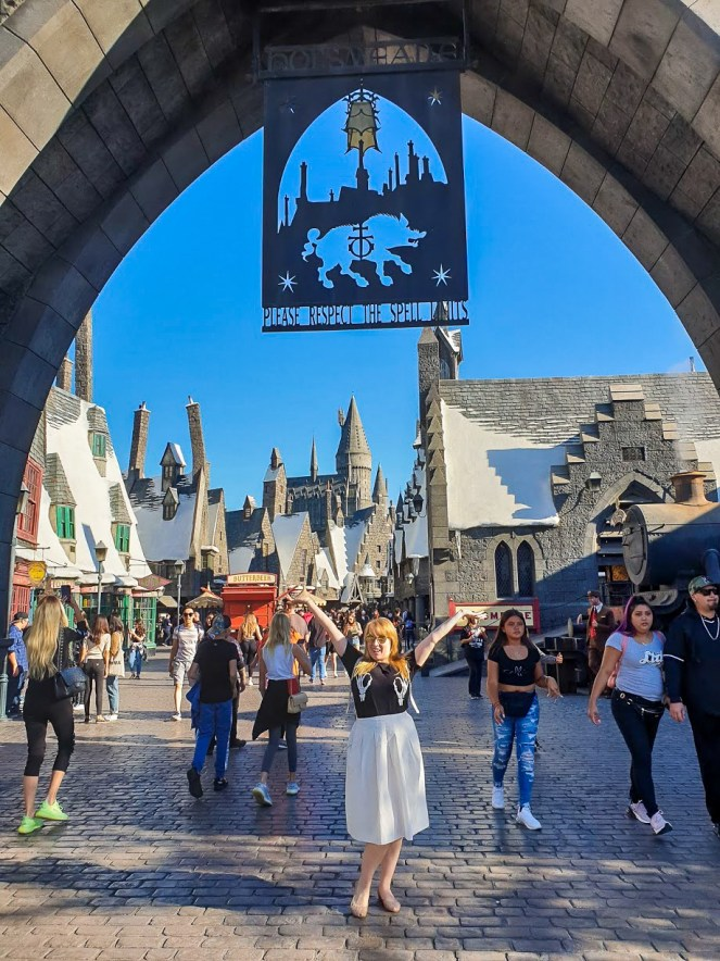 Rosie poses with her arms aloft for a photo beneath the Hogsmeade sign. Behind her, the roofs of Hogsmeade glisten with fake snow at Universal Studios Hollywood