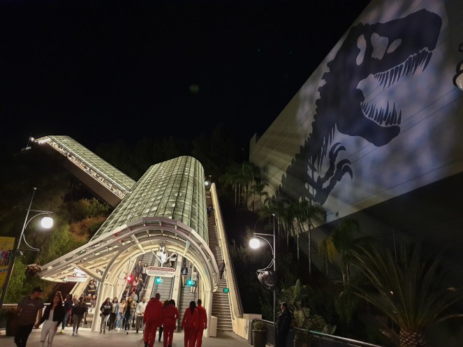 The escalators glow brightly against the dark sky and a huge shadow of a T-Rex skeleton is on the side of the Jurassic World ride at Universal Studios Hollywood