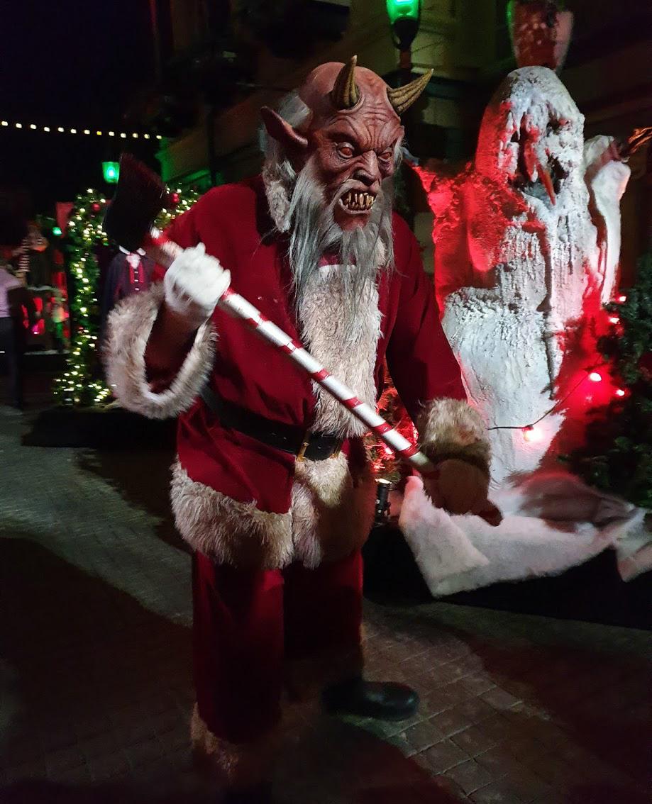 A demonic Father Christmas brandishing an axe at us