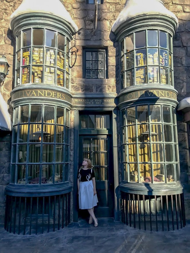 Rosie in the doorway of Ollivander's wand shop gazing wistfully at the window next to her