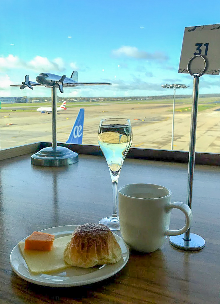 champagne and food by the window, overlooking the runway at No1 Lounge at London Gatwick South Terminal