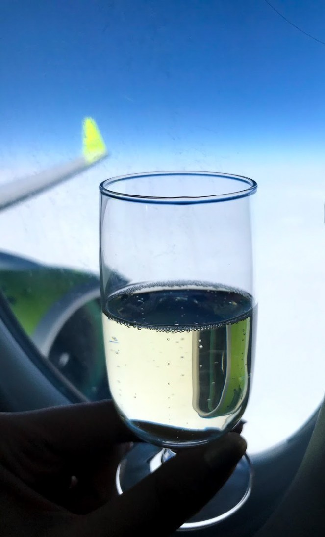 Champagne against the window of an airBaltic A220-300