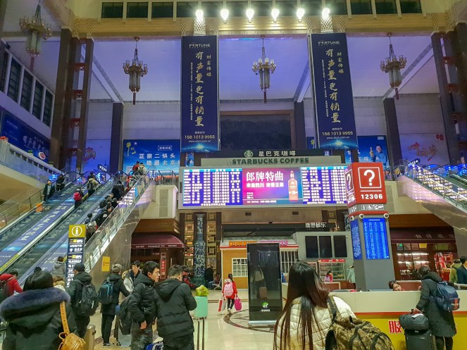 The inside of Beijing train station with boards everywhere and two sets of escalators to the second floor