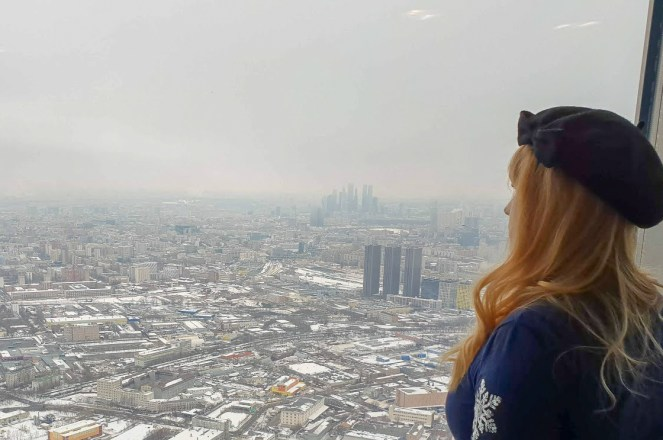 Rosie in a beret looks out of the window of Ostankino Tower in Moscow