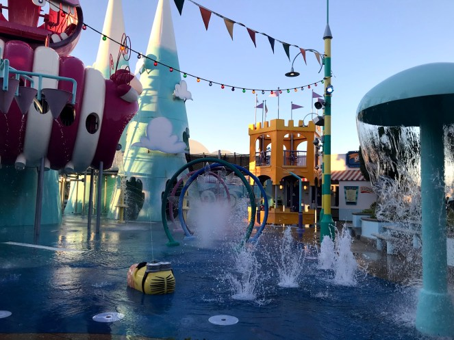 Water splashes in and around big colourful play areas