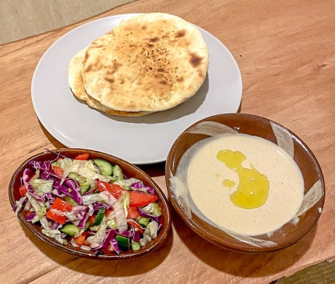 2 round flatbread, tahini dip and a pink, red and green salad at Aqua Sun, Gulf of Aqaba, Egypt