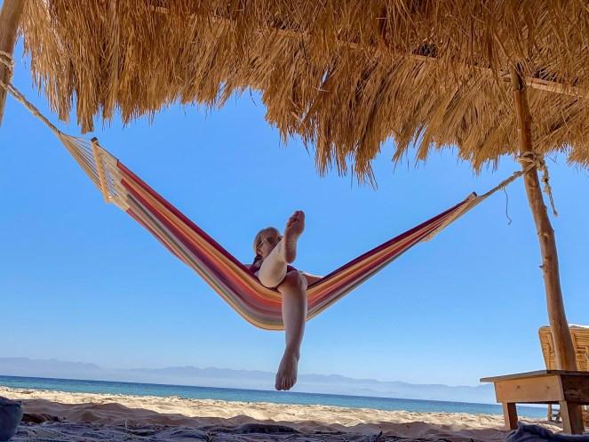 Rosie sitting in a hammock on the beach at Aqua Sun Beach Camp, Sinai, Egpyt