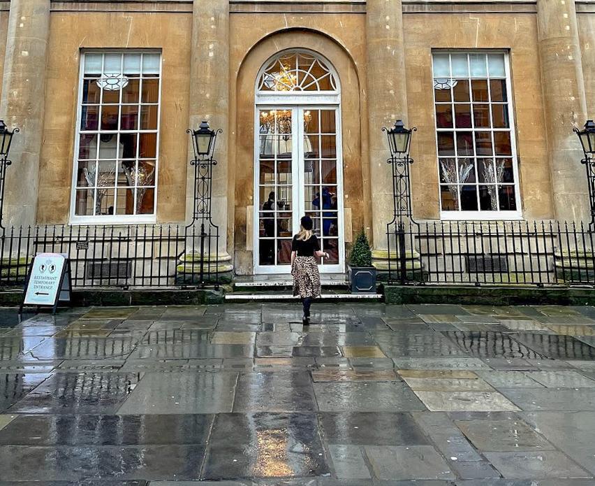 Rosie outside The Pump Room Bath, built with limestone and 4 corinthian columns