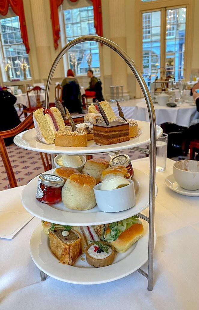The afternoon tea stand with savoury on the bottom, scones in the middle and sweet treats on the top plate at The Pump Room Bath