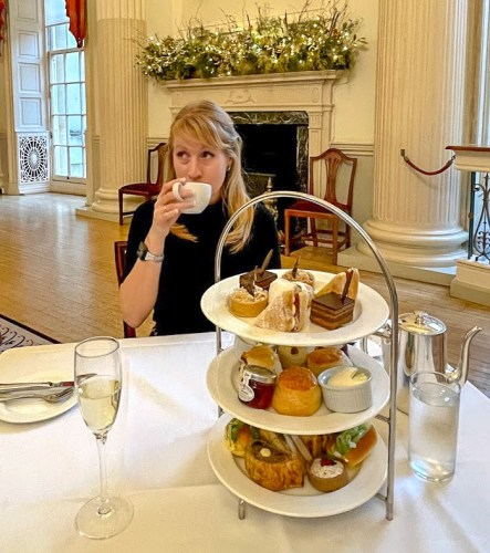 Rosie drinks from a white cup with afternoon tea in the foreground at The Pump Room Bath