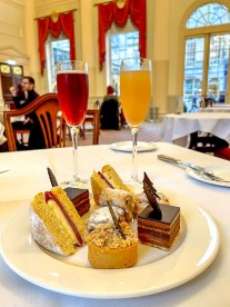 a selection of cakes, tarts and stollen on the sweet afternoon tea plate with Peach Bellini and the Pump Room Royale at The Pump Room Bath