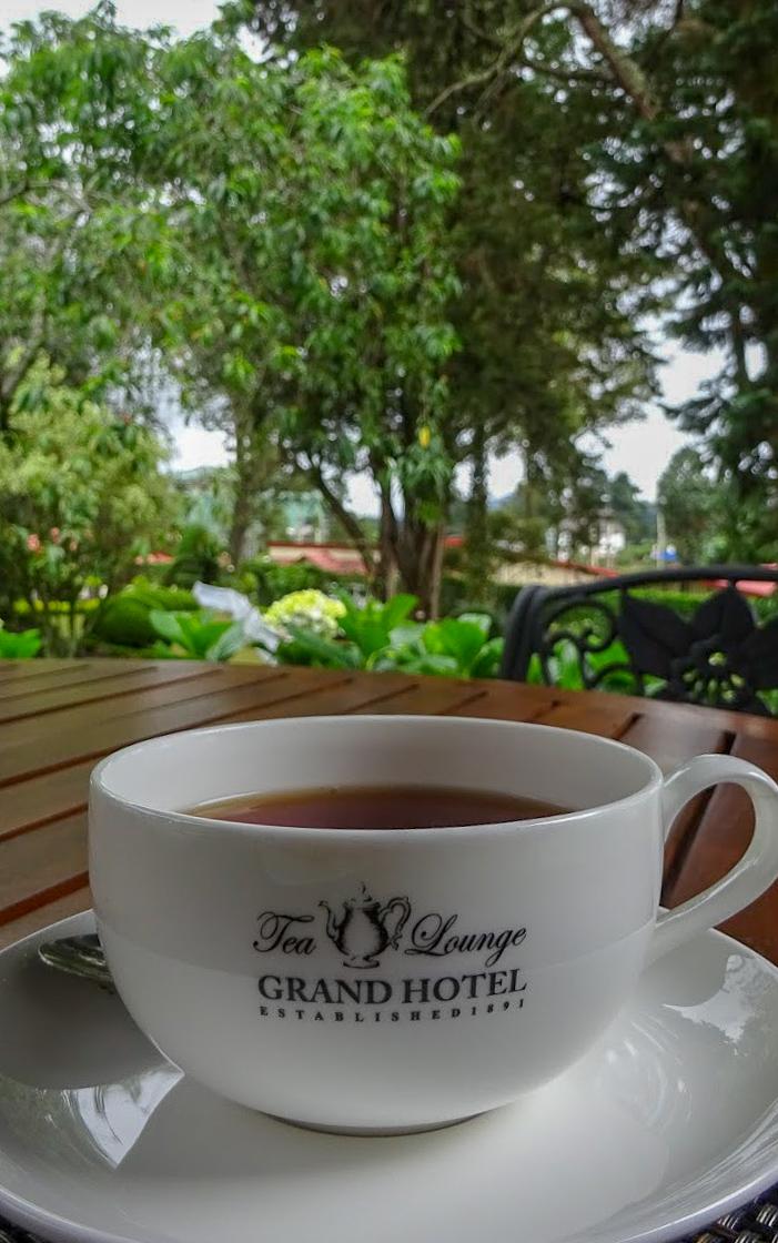a white cup of tea on a wooden table at The Grand Hotel, Nuwara Eliya, Sri Lanka